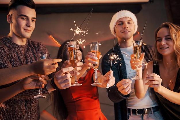 Een foto van een groep vrienden die plezier hebben met sneeuwmannen en champagne. gelukkig nieuwjaar. detailopname.