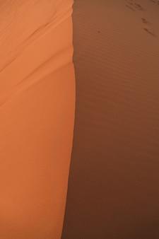 Een foto van een grote duin gesplitst door een lijn in het midden, licht aan de linkerkant en schaduwen aan de rechterkant. drone bekijk fotografie.