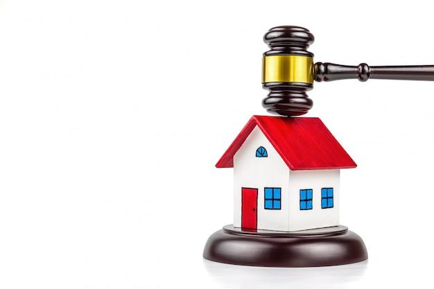 Een foto van een hamer en een huisje. deze fotoshoot in concept over vastgoedrecht