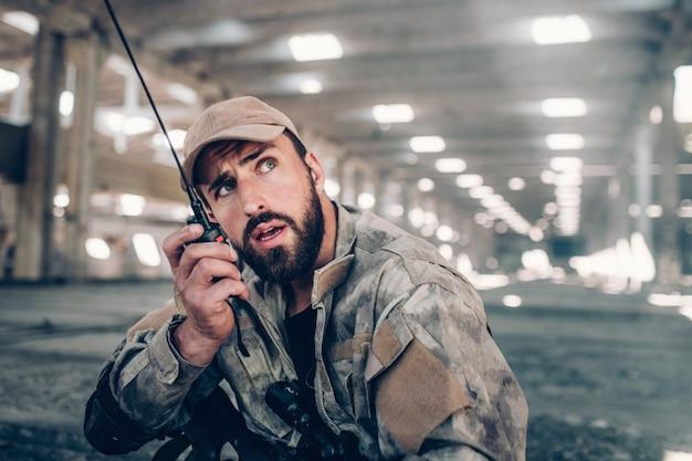 Een foto van een handige en aantrekkelijke soldaat die in draagbare radio spreekt. hij kijkt naar rechts en omhoog. guy draagt een speciaal uniform. hij is erg geconcentreerd. de mens heeft een pauze.