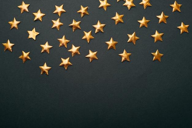 Een foto van een heleboel kleine gouden sterretjes in het bovenste deel van de foto en een vrije ruimte eronder