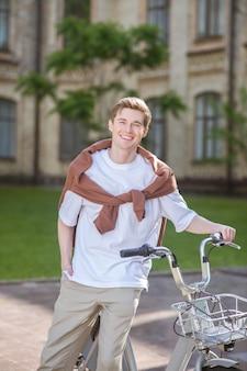 Een foto van een jonge kerel die bij de fiets staat