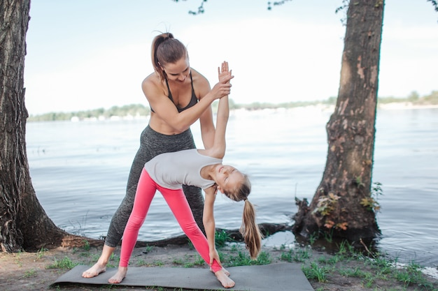 Een foto van een jonge leraar die haar leerling helpt om zich goed uit te rekken.