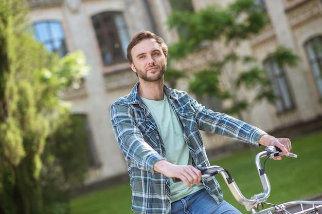Een foto van een jonge man in een geruit hemd op een fiets