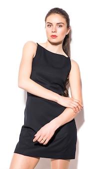 Een foto van een jonge mooie vrouw in een zwarte jurk die zich voordeed op witte achtergrond