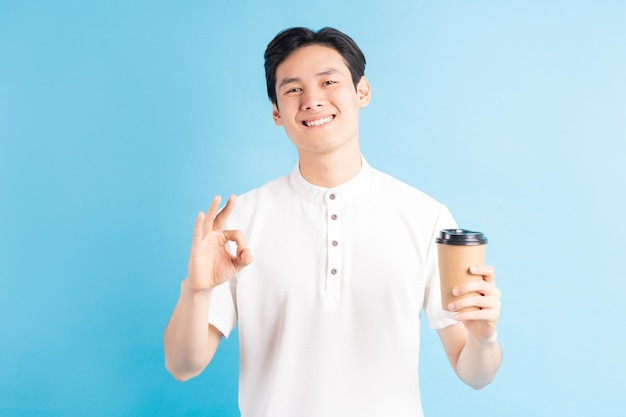 Een foto van een knappe aziatische jongen die een kartonnen beker in zijn hand houdt en een ok-symbool gebruikt