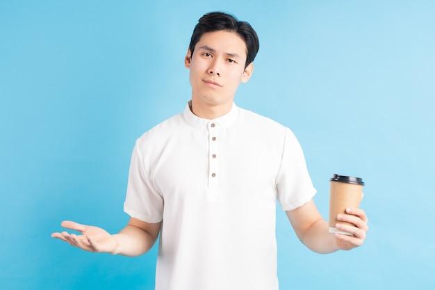 Een foto van een knappe aziatische jongen met een kartonnen beker in zijn hand met een verbaasde uitdrukking