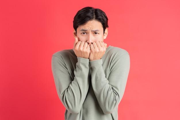 Een foto van een knappe aziatische man die zijn gezicht bedekt met zijn handen in angst