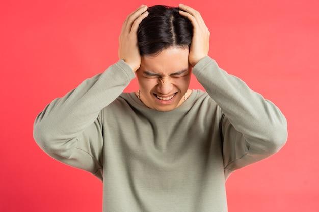 Een foto van een knappe aziatische man die zijn hoofd met beide handen vasthoudt in vermoeidheid