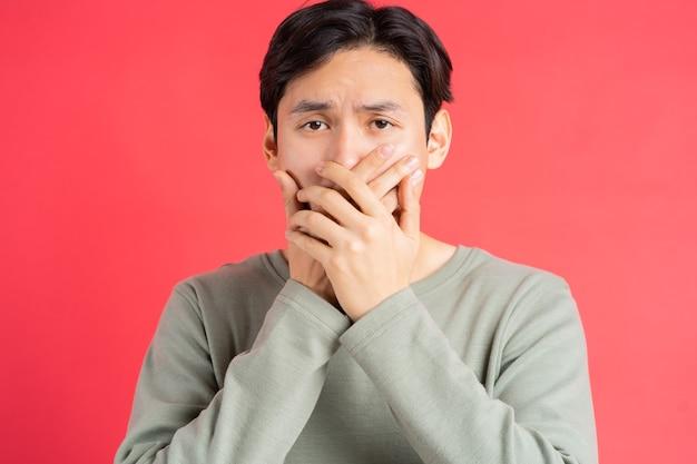 Een foto van een knappe aziatische man die zijn mond bedekt om het geheim van iemand anders niet te missen