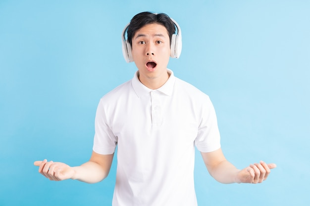 Een foto van een knappe aziatische man met een verbaasde uitdrukking die naar muziek luistert