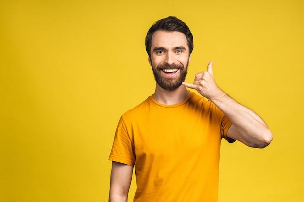Een foto van een knappe jonge, bebaarde man in casual geïsoleerd op een gele achtergrond die een gebaar maakt