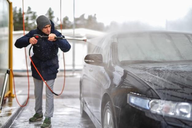 Een foto van een man die een auto wast onder hoge waterdruk buiten in het koude seizoen.