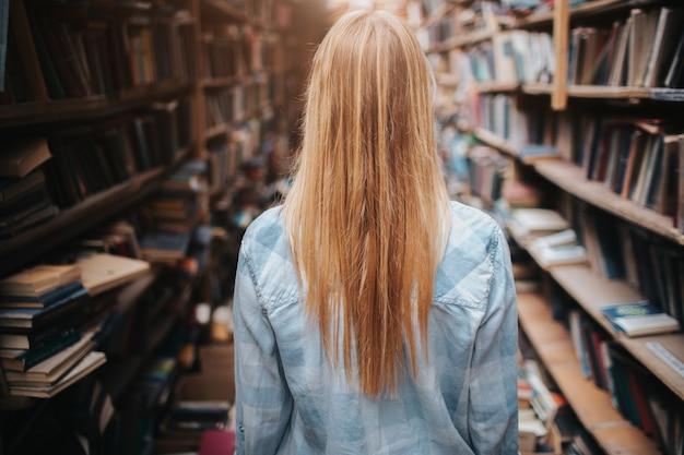 Een foto van een meisje dat tussen boekenkasten loopt met nieuwe en oude boeken. er is een puinhoop overal in de kamer. ze maakt een onderzoek.