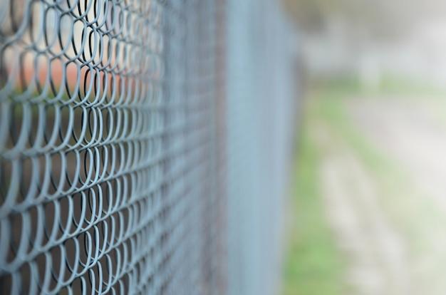 Een foto van een metalen net gebruikt als omheining van privébezit.