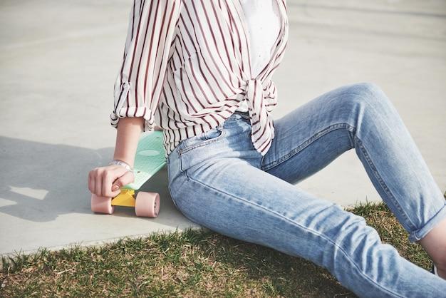 Een foto van een mooi meisje met mooi haar houdt een skateboard op een lang bord en lacht, stadsleven.