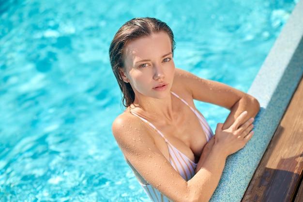 Een foto van een mooie jonge vrouw die tijd doorbrengt in een zwembad