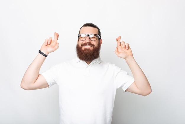 Een foto van een positieve jonge, bebaarde man die zijn vingers gekruist houdt, hoopt dat zijn wens uitkomt