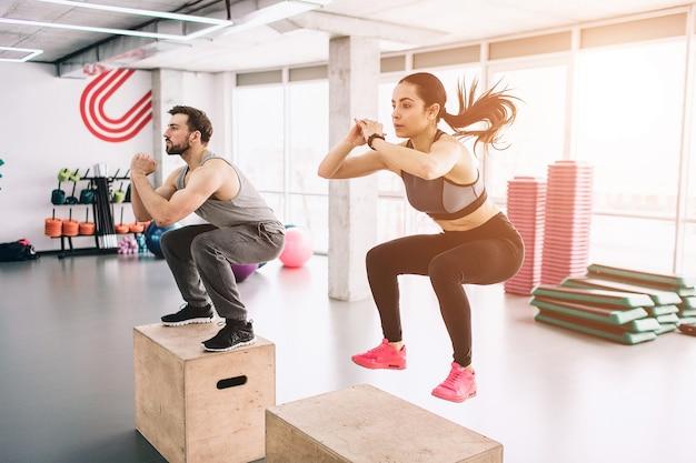 Een foto van een slanke en goed gebouwde jonge man en vrouw die sprongen op het platform doen