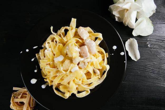 Een foto van een smakelijke maaltijd van spaghettis op een houten donkere tafel