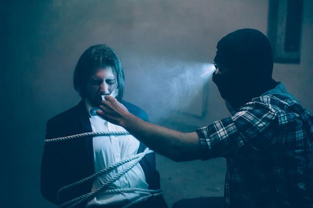 Een foto van een wrede ontvoerder die voor zijn slachtoffer zit en zijn mond opendoet