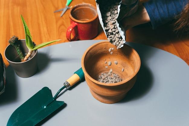Een foto van enkele steentjes die vrouw in een pot doet