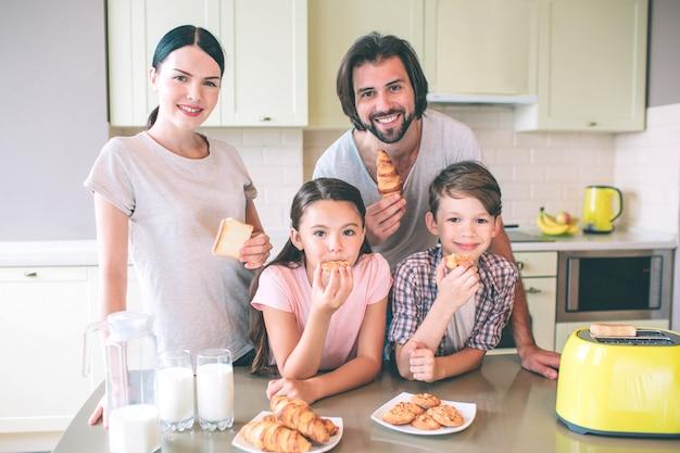 Een foto van familie staat aan tafel. ze kijken en poseren. meisje eant roll. jongens houden ze in handen. vrouw heeft stuk gebakken brood.