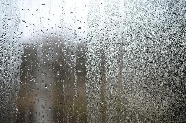 Een foto van het glazen oppervlak van het venster, bedekt met een veelheid aan druppels van verschillende grootte. achtergrondtextuur van een dichte laag van condensaat op glas