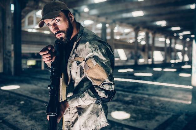 Een foto van het militaire man stellen. hij is in een grote hangar. hij houdt een zwart geweer vast en is klaar om te schieten. guy ziet er recht uit en blijft kalm. hij is erg stil.