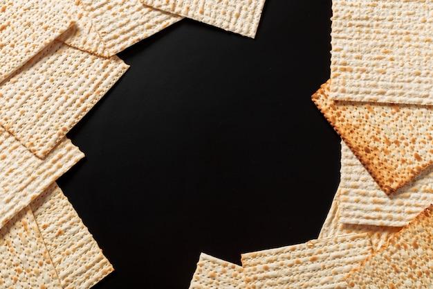 Een foto van matzah of matzastukken op zwarte achtergrond. matzah voor de joodse pesachvakanties. copyspace