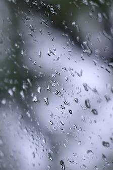 Een foto van regendalingen op het vensterglas met een vage mening van de tot bloei komende groene bomen.