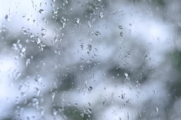Een foto van regendalingen op het vensterglas