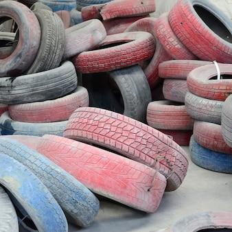 Een foto van veel oude gebruikte banden die op een vuilstort achtergelaten zijn
