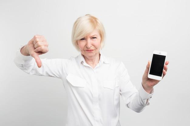 Een foto van volwassen dame met nieuwe smartphone. ze heeft het getest en toegegeven dat deze telefoon een slechte is. daarom toont ze een grote duim naar beneden.