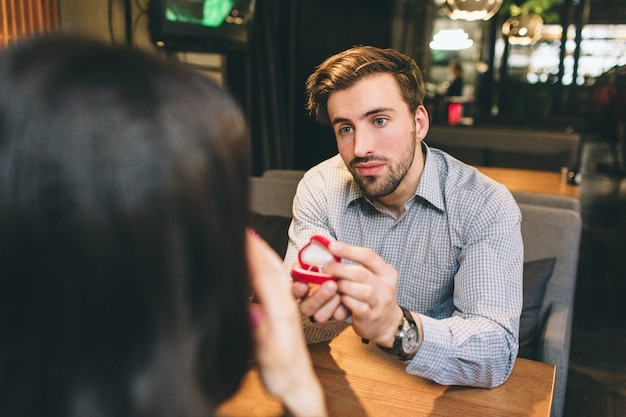 Een foto vanuit een andere hoek waarbij de aantrekkelijke man een voorstel doet aan zijn vriendin. hij is nerveus maar tegelijkertijd gelukkig.