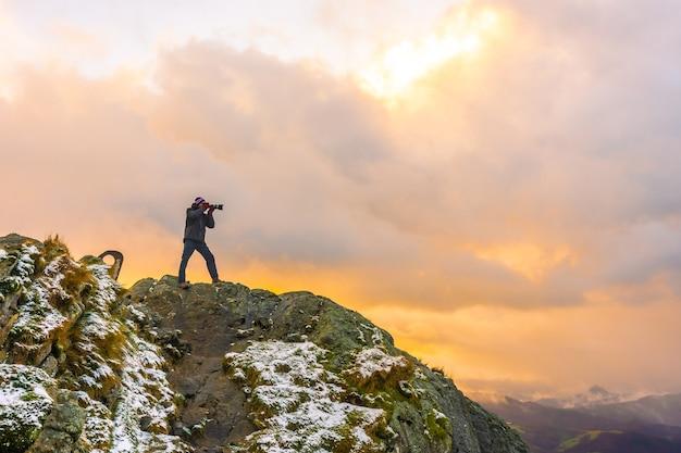 Een fotograaf bovenop de berg in de besneeuwde winteroranje zonsondergang, op de berg peñas de aya in de stad oiartzun bij san sebastian, spanje