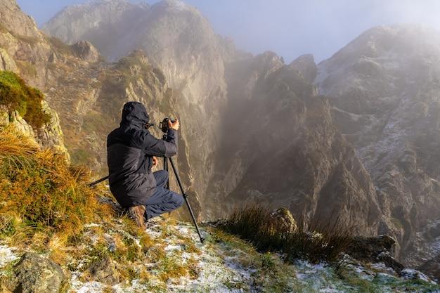 Een fotograaf die een foto maakt met het statief in de besneeuwde winterzonsondergang, op de berg van peñas de aya in de stad oiartzun nabij san sebastian, spanje
