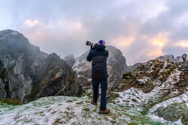 Een fotograaf die geniet van de besneeuwde winter, op de berg peñas de aya in de stad oiartzun nabij san sebastian, spanje