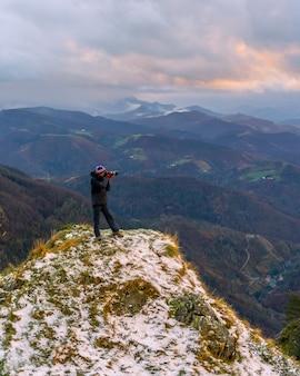 Een fotograaf die uitkijkt vanaf de besneeuwde top, op de berg peñas de aya in de stad oiartzun nabij san sebastian, spanje