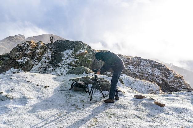 Een fotograaf die zich klaarmaakt in de besneeuwde winterzonsondergang op de berg peñas de aya in de stad oiartzun nabij san sebastian, spanje