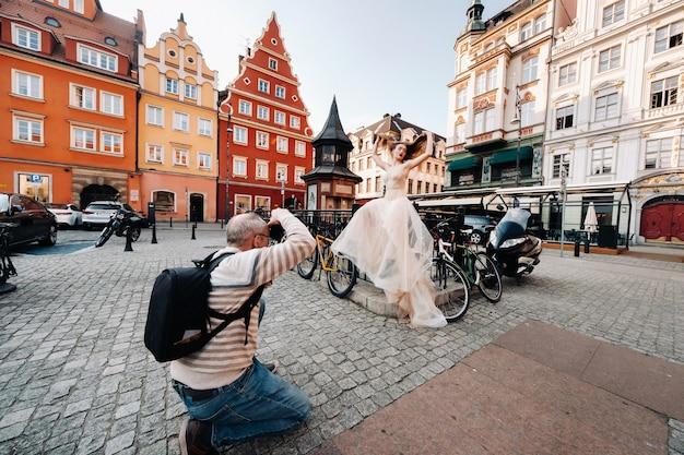 Een fotograaf fotografeert een bruid in een trouwjurk met lang haar in de oude binnenstad van wroclaw. bruiloft fotoshoot in het centrum van een oude poolse stad. wroclaw, polen.