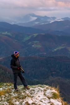 Een fotograaf kijkt naar het uitzicht op de met sneeuw bedekte top, op de berg peñas de aya in de stad oiartzun nabij san sebastian, spanje