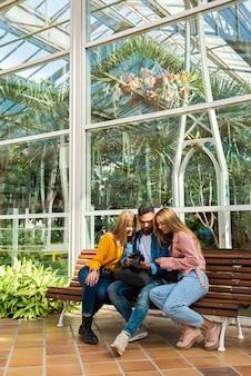 Een fotograaf toont zijn werk in zijn camera aan twee jonge meisjes die op een houten bank zitten. de afbeelding is een combinatie van warme kleuren, helder natuurlijk licht en ruimte voor tekst