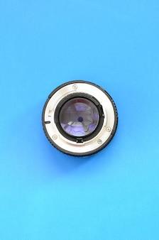 Eén fotografische lens ligt op een helderblauwe achtergrond. ruimte voor tekst