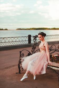 Een fragiele ballerina in een lange roze jurk met een volle organza rok zit op een smeedijzeren houten bank...