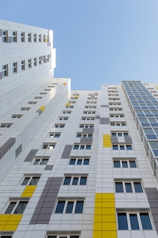 Een fragment van de gevel van een gebouw met meerdere verdiepingen. wit-grijze geventileerde gevel van een modern onherkenbaar gebouw. perspectief omhoog. verticaal