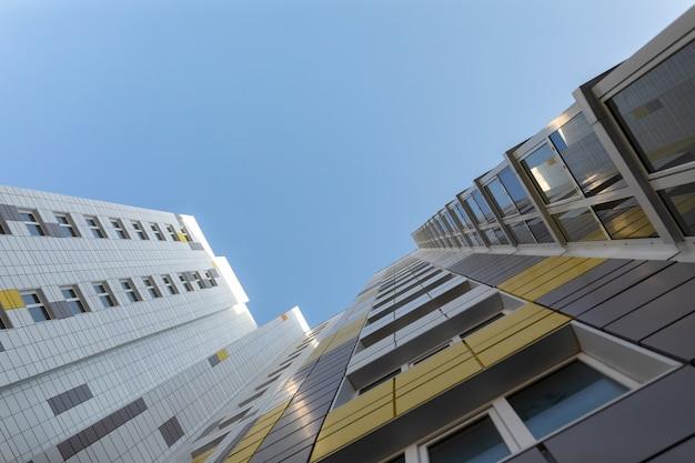 Een fragment van de gevel van een gebouw met meerdere verdiepingen witgrijze geventileerde gevel van een modern onherkenbaar gebouw perspectief omhoog