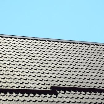 Een fragment van een dak van een metalen tegel met een donkerrode kleur. kwaliteits dakbedekking