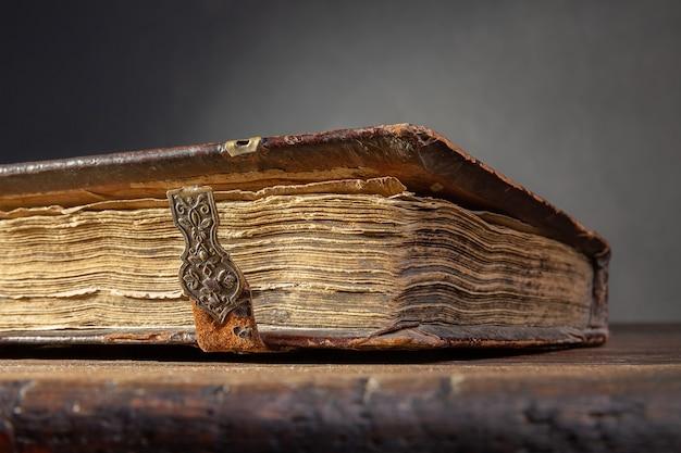 Een fragment van een oud bruin boek met gespen en gele pagina's op een oude houten tafel
