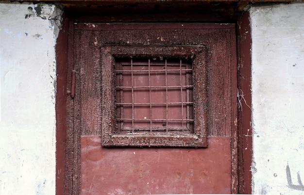 Een fragment van een oude deur met een tralieraam